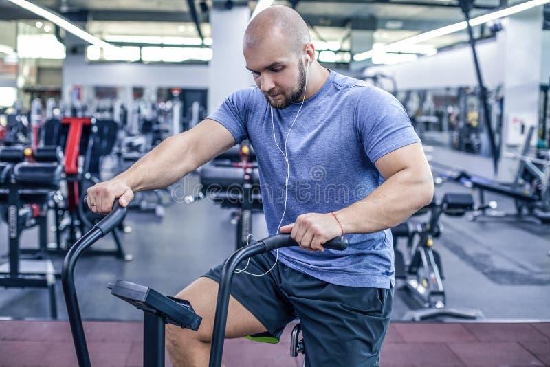 Atleta joven que usa la bicicleta est?tica en el gimnasio Varón de la aptitud que usa la bici del aire para el entrenamiento card imagen de archivo libre de regalías