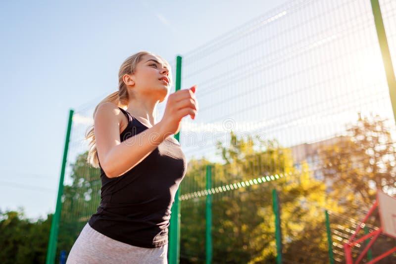 Atleta juguetón joven de la mujer que corre en sportsground en verano El activar al aire libre Manera de vida sana fotos de archivo
