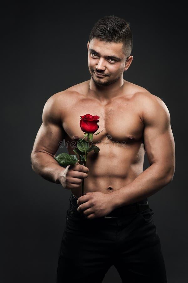 Atleta Man com Rose Flower, menino atlético com o retrato despido muscular do estúdio do corpo imagem de stock royalty free