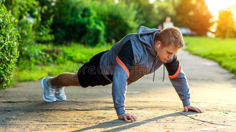 Atleta maschio che si esercita nel parco Ritratto di un tipo maschio che fa spinta-UPS Il concetto di uno stile di vita sano resi immagini stock libere da diritti