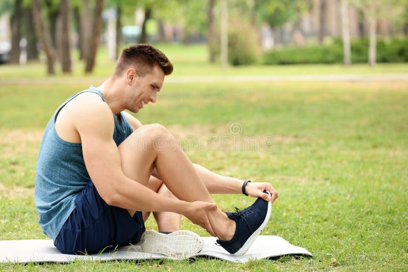 Atleta maschio che soffre dal dolore del piede durante l'addestramento fotografia stock