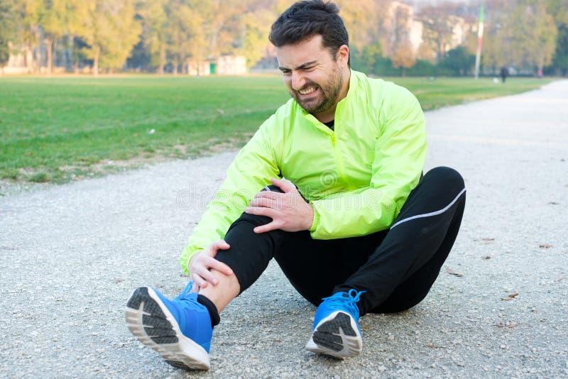 Atleta maschio che soffre dal dolore in gamba mentre esercitarsi all'aperto fotografia stock libera da diritti