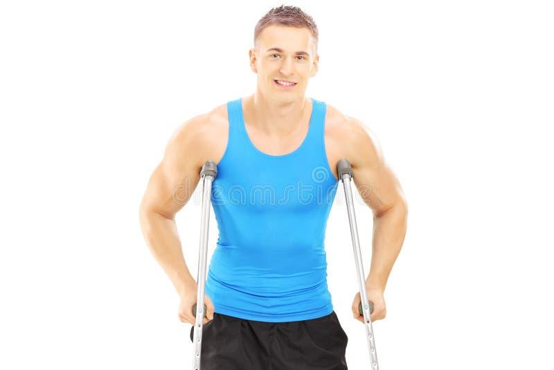 Atleta maschio danneggiato con le grucce fotografia stock libera da diritti