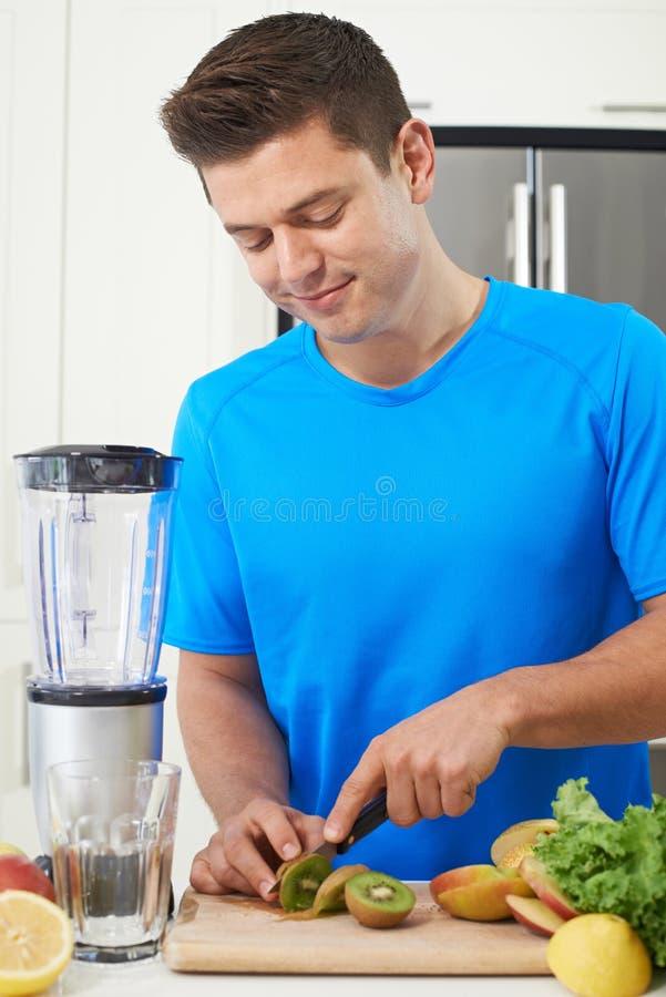 Atleta maschio Making Juice Or Smoothie In Kitchen fotografie stock libere da diritti