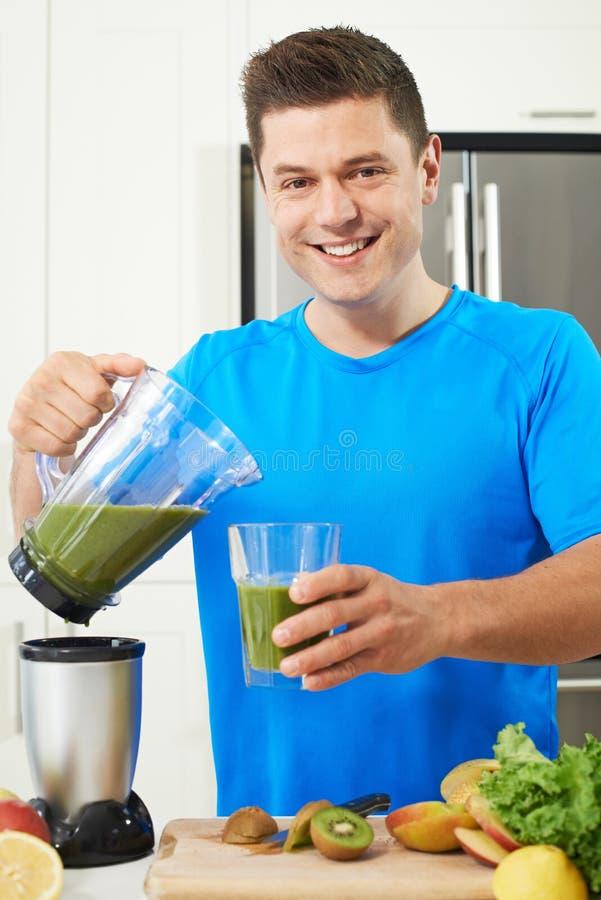 Atleta maschio Making Juice Or Smoothie In Kitchen immagine stock libera da diritti