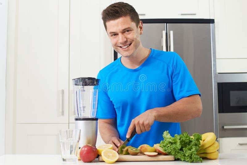 Atleta maschio Making Juice Or Smoothie In Kitchen immagini stock libere da diritti