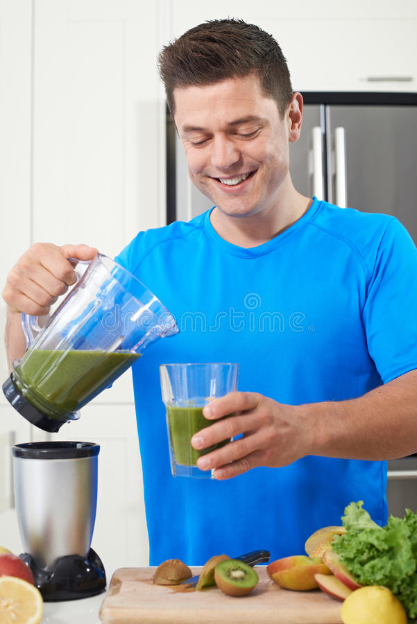 Atleta maschio Making Juice Or Smoothie In Kitchen fotografie stock