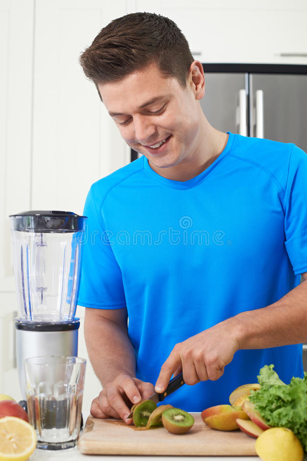 Atleta maschio Making Juice Or Smoothie In Kitchen fotografia stock libera da diritti
