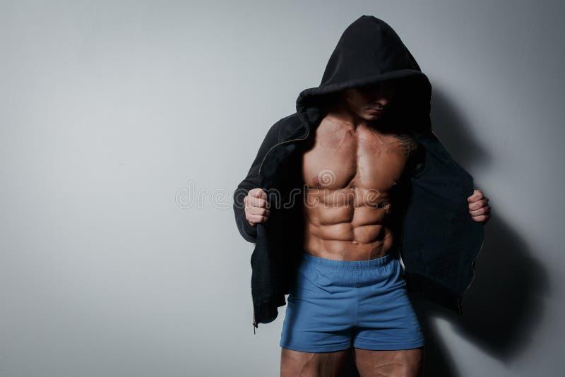 Atleta masculino bombeado atlético no hoodie no fundo cinzento imagens de stock