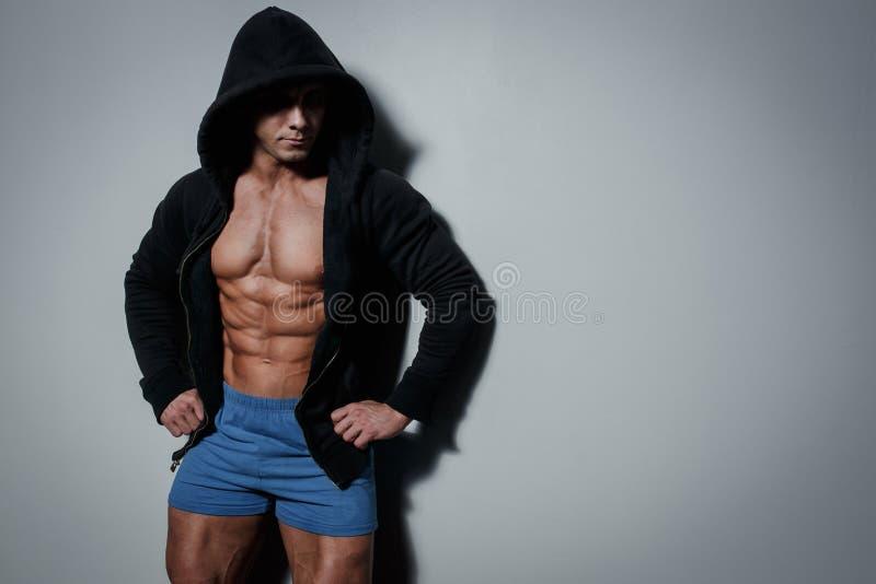 Atleta masculino bombeado atlético no hoodie no fundo cinzento foto de stock