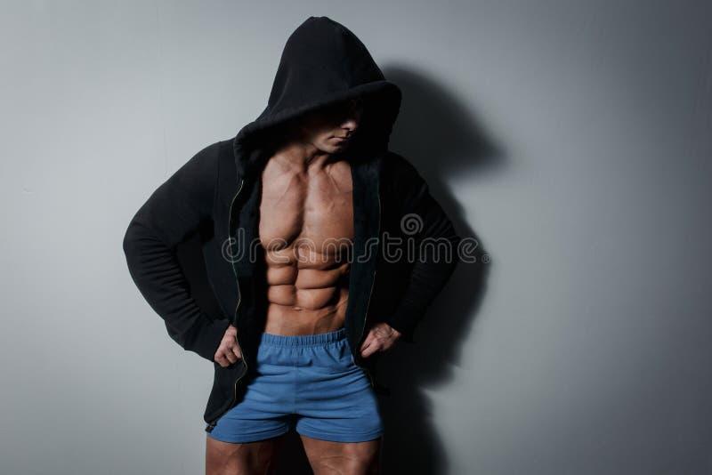Atleta masculino bombeado atlético no hoodie no fundo cinzento imagens de stock royalty free