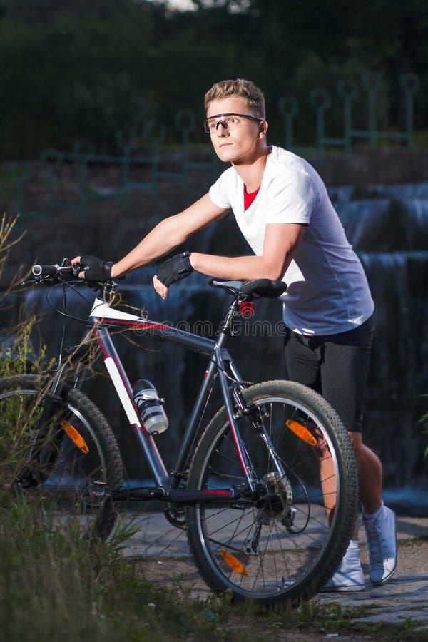 Atleta masculino caucasiano com o Mountain bike que levanta contra a cachoeira foto de stock royalty free