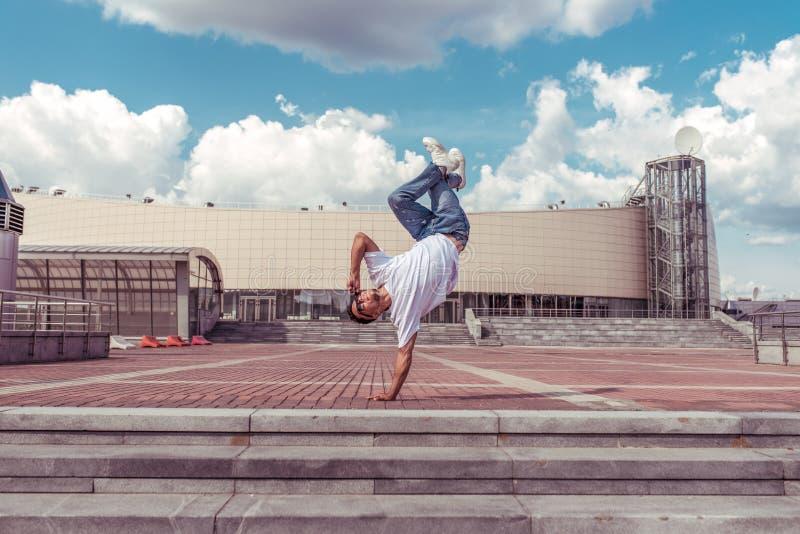 Atleta masculino, dançarina de verão Um salto de braço em pé Rápido estilo moderno de dança moderna e fascinante, ginástica imagem de stock