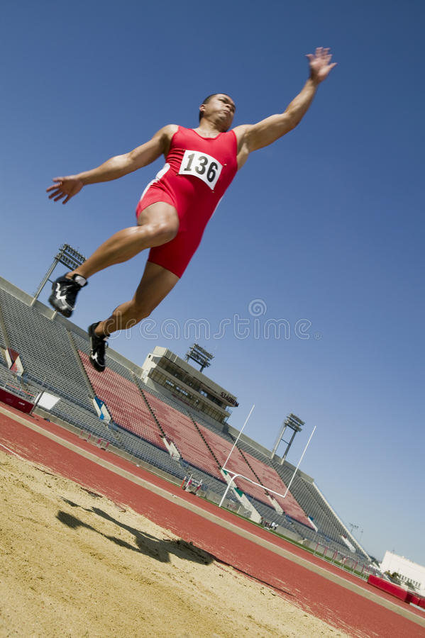 Atleta masculino Doing um salto longo fotografia de stock royalty free