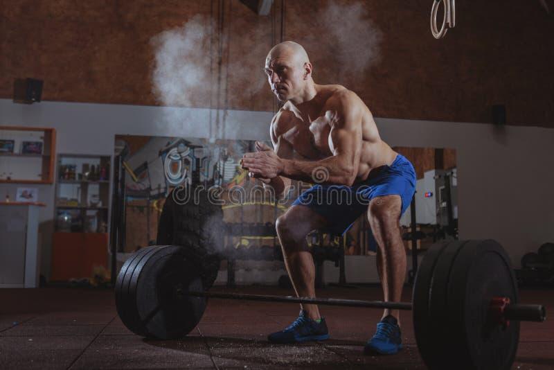Atleta masculino forte do crossfit que exercita com barbell pesado imagem de stock