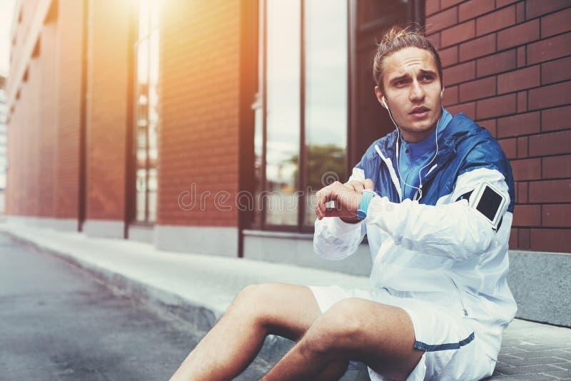 Atleta masculino no windrunner azul que senta-se na rua que ajusta o programa de corrida para seu exercício da manhã usando relóg imagem de stock