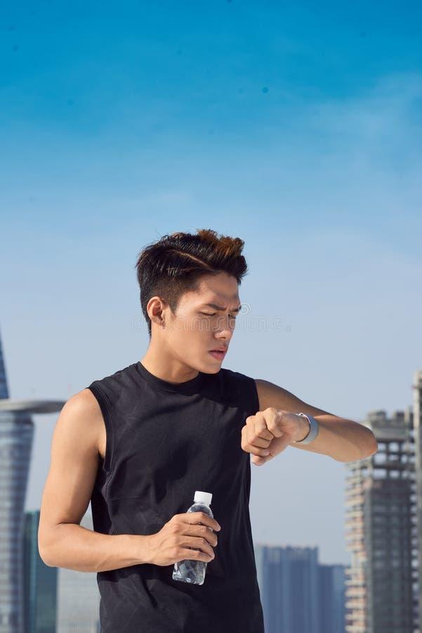 Atleta masculino novo que verifica o smartwatch, sobre a opini?o do ombro imagem de stock royalty free