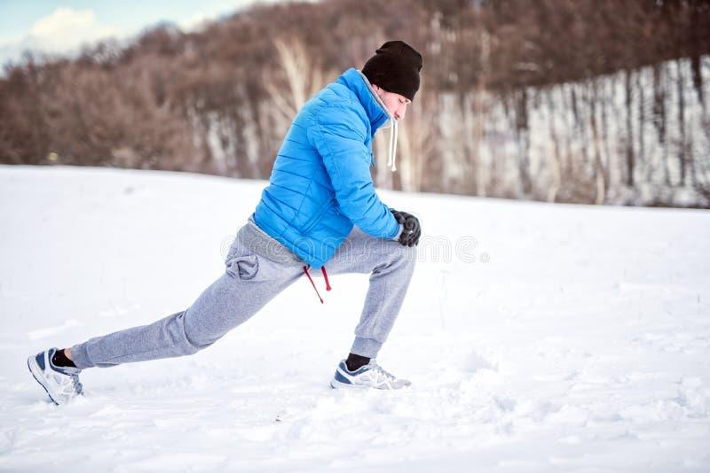 Atleta masculino que estica na neve foto de stock royalty free
