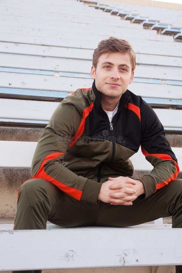 Atleta masculino que senta-se nos bleachers foto de stock