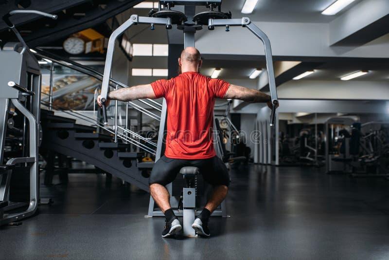 Atleta muscolare sulla macchina di esercizio, vista posteriore fotografia stock