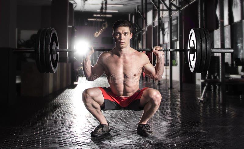 Atleta muscular atractivo del crossfit que hace ejercicio agazapado en el MES fotografía de archivo libre de regalías