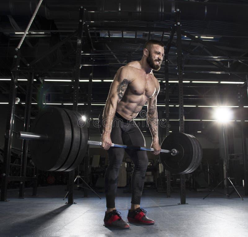 Atleta muscular atractivo que hace ejercicio pesado del deadlift en la MOD foto de archivo libre de regalías