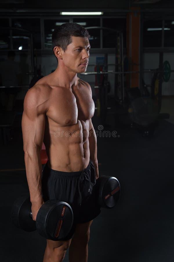 Atleta muscular bronceado con pesas de gimnasia pesadas fotografía de archivo libre de regalías