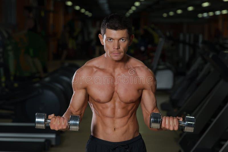 Atleta muscular bronzeado com pesos, vista dianteira imagem de stock