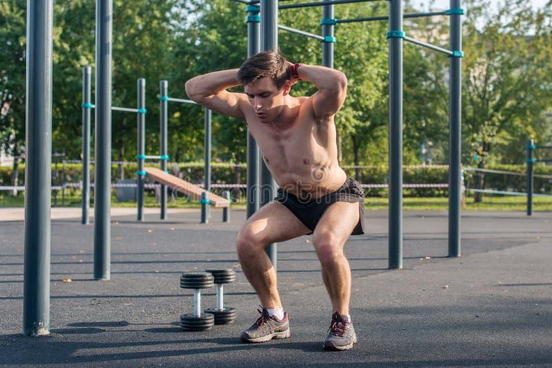Atleta muscular da aptidão que faz ocupas com suas mãos atrás da cabeça que exercita no parque fotos de stock