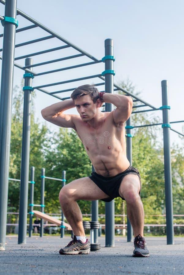 Atleta muscular da aptidão que faz ocupas com suas mãos atrás da cabeça que exercita no parque imagens de stock