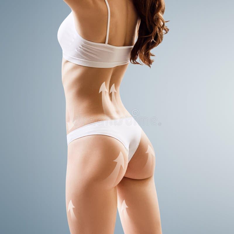 Atleta muscular de la mujer joven con las flechas de elevación en cuerpo imagen de archivo