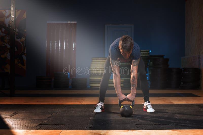 Atleta muscular de sexo masculino que ejercita con el kettlebell imagen de archivo