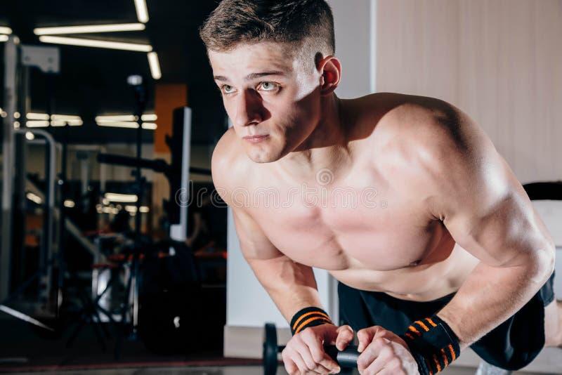 Atleta muscular novo que faz flexões de braço imagem de stock royalty free
