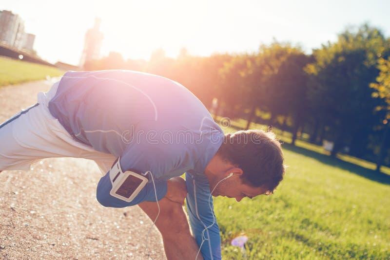 Atleta na camisa azul que faz esticando o aquecimento antes do exercício imagens de stock