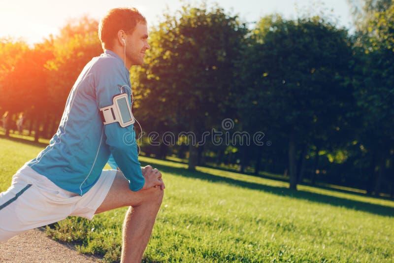 Atleta na camisa azul que faz o aquecimento antes do exercício no parque imagem de stock royalty free