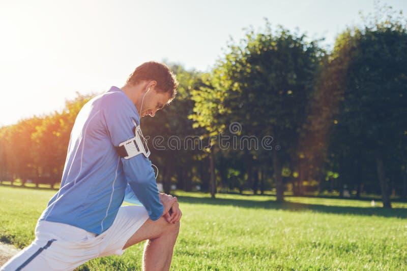 Atleta na camisa azul que faz os pés que esticam o aquecimento antes do exercício fotografia de stock