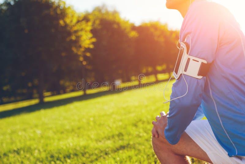 Atleta na camisa azul que faz os pés que esticam o aquecimento antes do exercício no parque foto de stock
