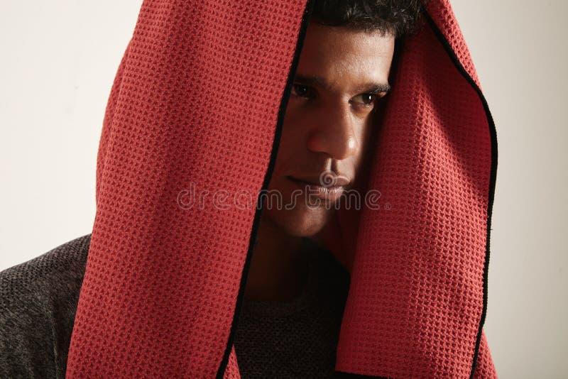 Atleta nero con l'asciugamano rosso che copre il suo capo fotografie stock