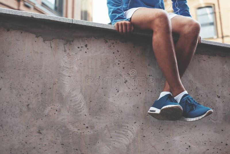 Atleta nos tênis de corrida azuis que sentam-se e que descansam após a sessão do exercício da rua fotos de stock