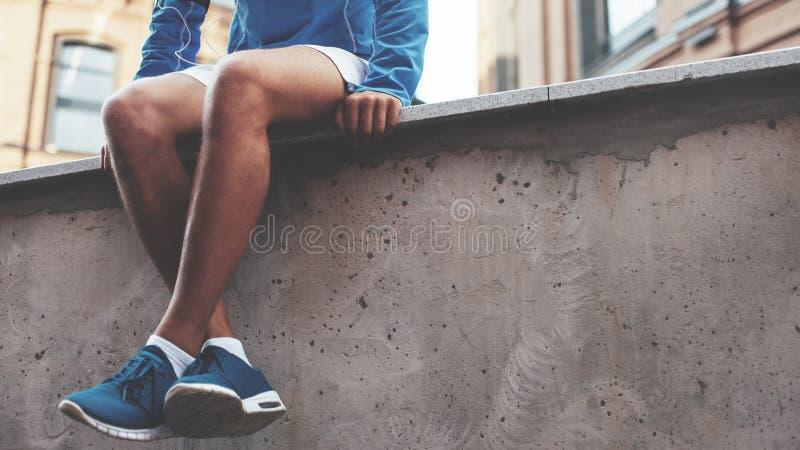 Atleta nos tênis de corrida azuis que sentam-se e que descansam após a sessão dura do exercício da rua imagens de stock royalty free