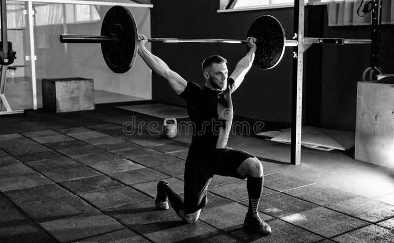 Atleta novo apto que levanta o barbell no gym Treinamento do Gym fotos de stock