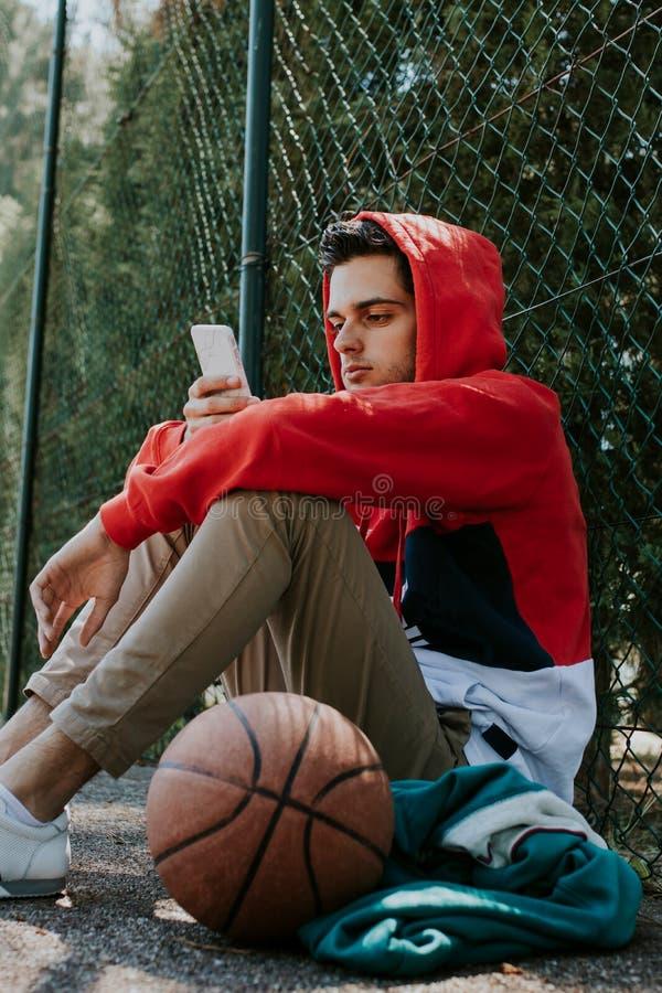 Atleta novo com móbil exterior foto de stock