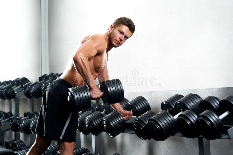 Atleta novo considerável que dá certo no gym fotografia de stock