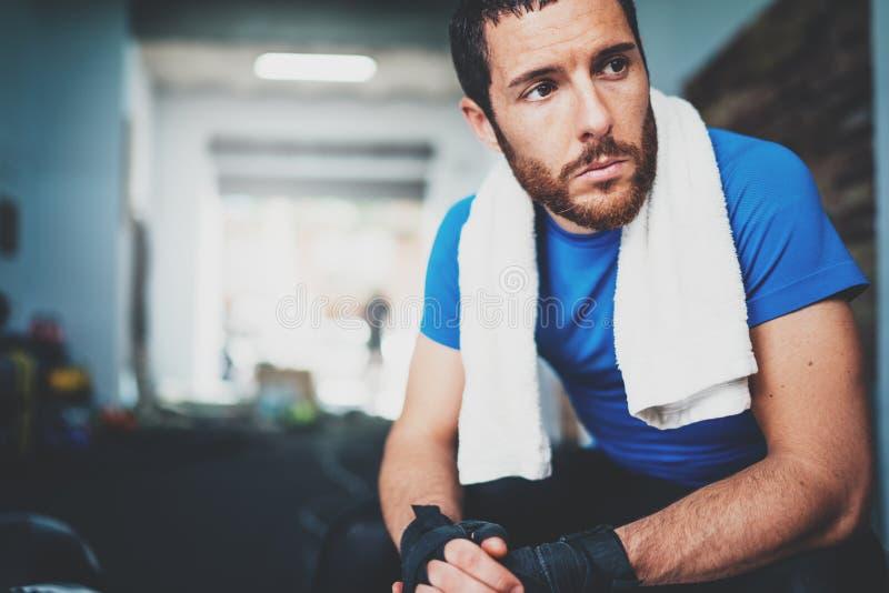 Atleta novo de Overexhausted que senta-se nas ataduras pretas do encaixotamento Homem do pugilista que relaxa após o treinamento  fotografia de stock