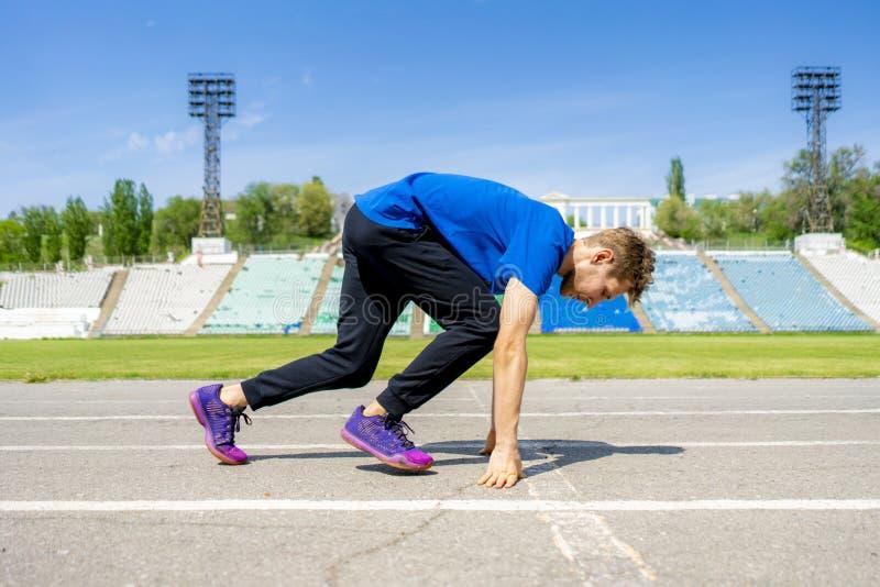 Atleta novo do corredor na baixa posição do começo sobre a trilha dos esportes no estádio exterior fotografia de stock