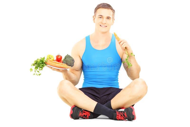 Atleta novo no assoalho que mantém um prato completo dos legumes frescos a imagem de stock
