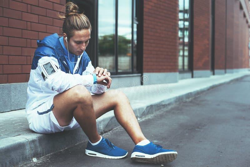 Atleta novo no windrunner azul que senta-se na rua que ajusta o programa de corrida para seu exercício da manhã usando relógios e fotografia de stock