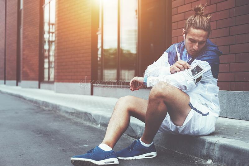 Atleta novo no windrunner azul que senta-se na rua que ajusta o programa de corrida para seu exercício da manhã usando o telefone fotos de stock