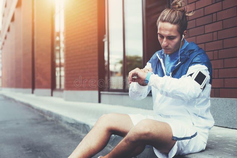 Atleta novo no windrunner azul que senta-se na rua que ajusta o programa de corrida para seu exercício do amanhecer usando relógi imagem de stock royalty free
