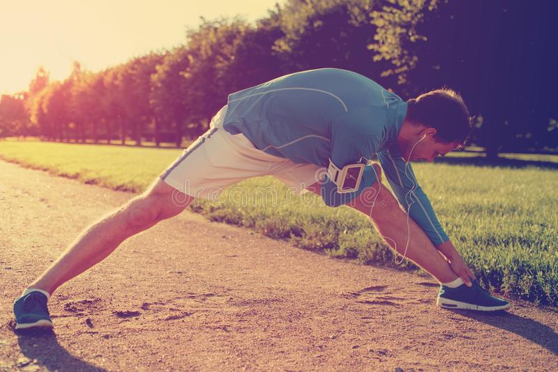 Atleta novo que faz o esticão de aquecimento antes do exercício no parque fotografia de stock